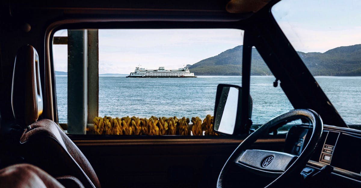 A view of a car window in front of a body of water